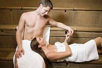 Woman resting head on boyfriendÆs lap in sauna