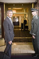 Businessman and bellhop in hotel doorway