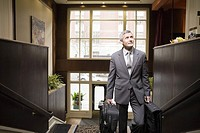 Businessman carrying suitcases up stairs