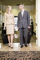Couple pulling suitcases in lobby