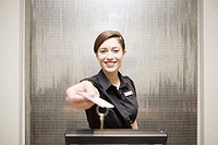 Female hotel front desk clerk handing keycard