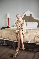 Businesswoman sitting on edge of bed