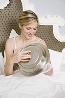 Woman holding room service plate in bed