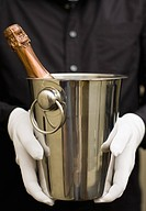 Waiter holding champagne in ice bucket