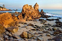 Sunset on breaking waves and rocks at Corona Del Mar beach. Newport Beach. California. USA