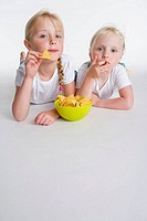 Two blond girls eating chips