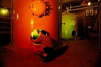 Worker inspecting chemical holding tank, water treatment plant