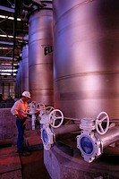 Worker around chemical tanks in chemical plant. USA