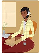 Businesswoman wearing a telephone headset and taking notes