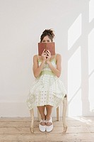 Woman hiding behind a book (thumbnail)