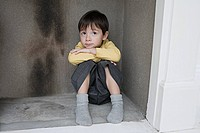 Boy hiding in a fireplace