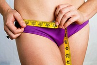 Closeup of young woman in purple bikini measuring her hips. In studio.