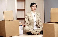 Businesswoman on desk among boxes meditating