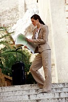 Businesswoman with a map and suitcase