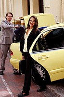 Businessman and woman loading taxi