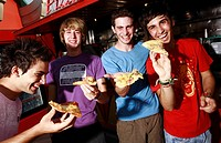 Male teenagers hanging out, eating pizza