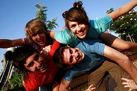 Teenagers playing on piggy back in amusement park