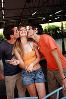 Two male teenagers kissing female teenager
