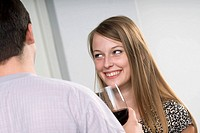 young woman having glass of wine and flirting with man