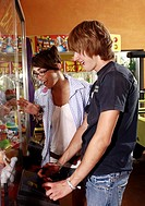 Teenage couple playing game in amusement park