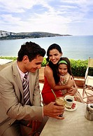 Couple with daughter at seaside cafe table