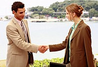 Man and woman shaking hands at seaside meeting