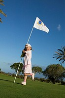 full boy portrait of little girl holding flag on golf course