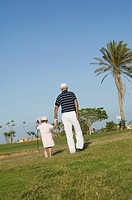 mature golf player and grandchild on golf course