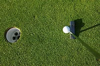 still life of golf hole ball and club