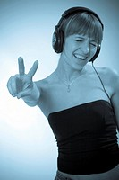 Woman showing victory by fingers, with earphones on her head