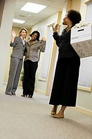 Businesswomen waving goodbye to a pregnant businesswoman in the office