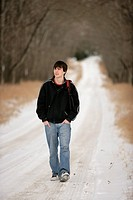 A teenage boy walking on a snow-covered path