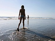 Young girl walking in the water's edge. Atlantic ocean