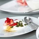 Yoghurt with strawberries and pistachios, close-up