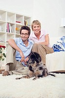 Couple in living room, with dog, portrait