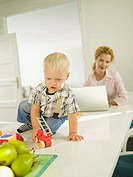 Mother and baby boy 12-24 months, mother using laptop