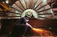 Factory worker grinding metal with huge saw blade in background, Vancouver. British Columbia, Canada