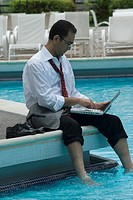 Hispanic businessman using laptop next to swimming pool