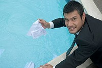 Hispanic businessman holding wet paperwork