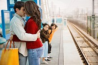 Hispanic couple hugging at train station