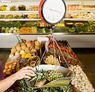 Hispanic man weighing pineapple in grocery store