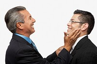 Hispanic businessman smiling at younger businessman