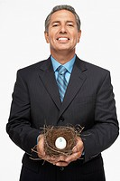 Hispanic businessman holding nest with dollar sign egg