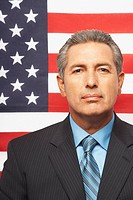 Hispanic businessman in front of American flag
