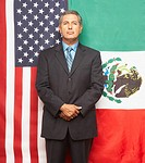 Hispanic businessman in front of American and Mexican flags
