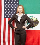 Hispanic businesswoman in front of American and Mexican flags