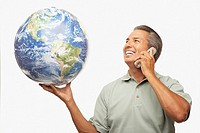 Hispanic man holding globe and talking on cell phone
