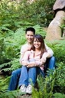 Asian couple hugging in woods