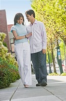 Hispanic couple walking on sidewalk