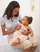 African American mother drying off baby (thumbnail)